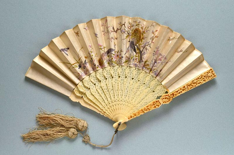 A Chinese ivory folding fan with double paper leaf and ornately carved guardstick made for export in China in 1870.